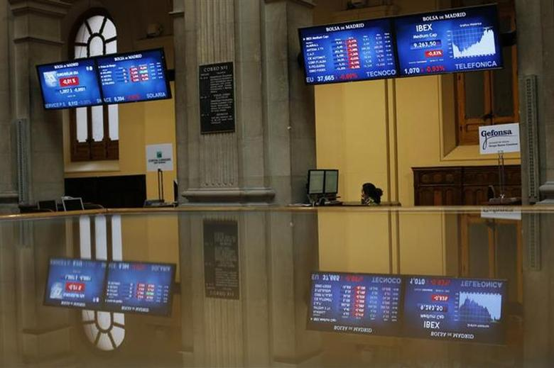 A trader looks at computer screens at Madrid's Bourse March 26, 2013. REUTERS/Susana Vera/Files