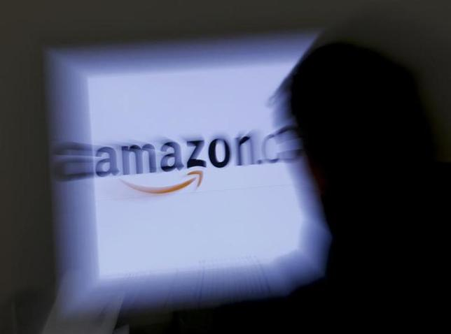 A zoomed illustration image of a man looking at a computer monitor showing the logo of Amazon is seen in Vienna November 26, 2012. To match Special Report TAX-AMAZON REUTERS/Leonhard Foeger