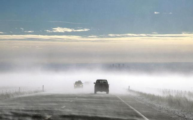 Vehicles make their way through a ground blizzard on a highway leading to Denver, Colorado with the city skyline barely seen in the background January 30, 2013. REUTERS/Rick Wilking