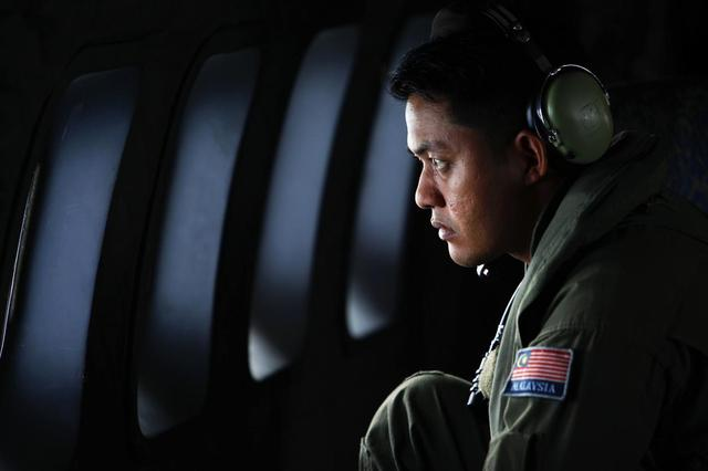 A crew member from the Royal Malaysian Air Force looks through the window of a Malaysian Air Force CN235 aircraft during a Search and Rescue (SAR) operation to find the missing Malaysia Airlines flight MH370, in the Straits of Malacca March 13, 2014. REUTERS/Samsul Said