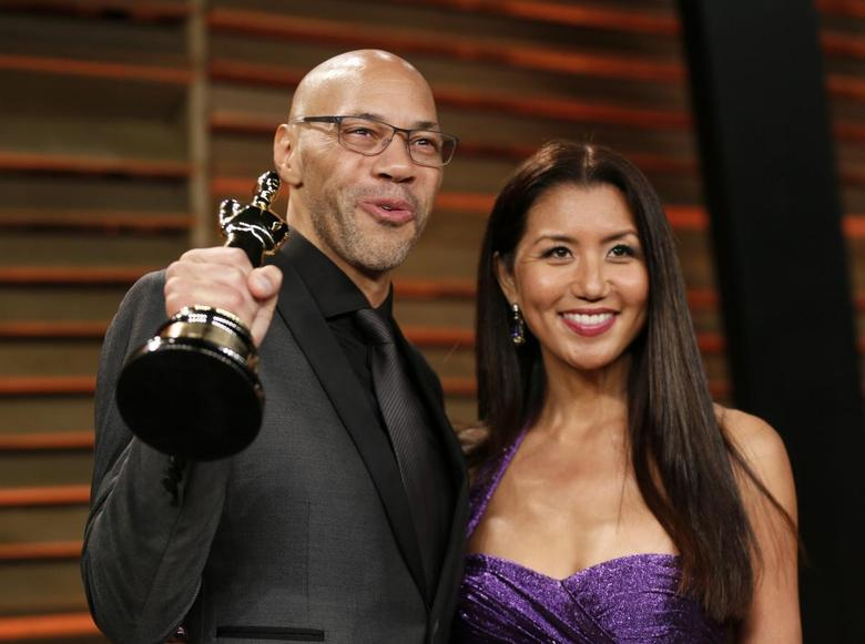 Writer John Ridley holds up his award for best adapted screenplay for ''12 Years a Slave'' as he arrives with his wife Gayle at the 2014 Vanity Fair Oscars Party in West Hollywood, California March 3, 2014. REUTERS/Danny Moloshok