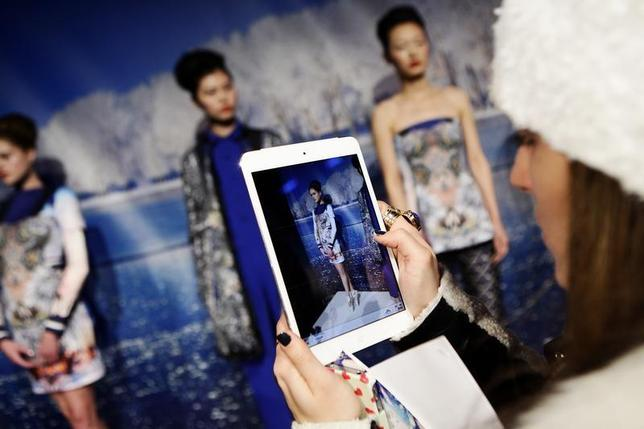 A woman takes a photo of models presenting creations from the Clover Canyon Autumn/Winter 2013 collection during New York Fashion Week, February 13, 2013. REUTERS/Joshua Lott