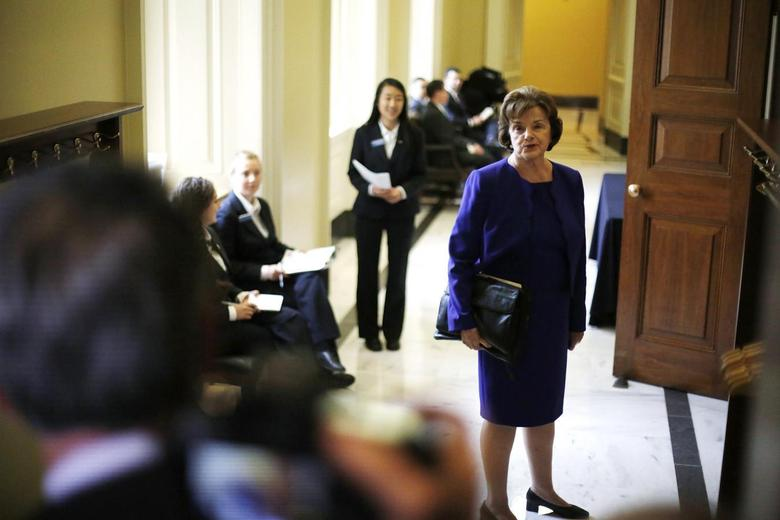U.S. Senator Dianne Feinstein (D-CA) turns to talk to reporters as she walks to the weekly Democratic caucus policy luncheon at the U.S. Capitol in Washington March 11, 2014. A dispute between the Central Intelligence Agency and a U.S. Senate committee that oversees it burst into the open on Tuesday when Feinstein accused the agency of spying on Congress and possibly breaking the law. REUTERS/Jonathan Ernst