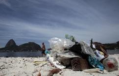 Homem caminha próximo a lixo na baía de Guanabara, no Rio de Janeiro, local que receberá a Olimpída de 2016. Foto de 12 de março de 2014. REUTERS/Sergio Moraes