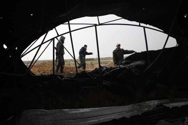 Members of the Palestinian security forces loyal to Hamas inspect the damage after Israeli air strikes on smuggling tunnels in Rafah in the southern Gaza Strip March 13, 2014. REUTERS/Ibraheem Abu Mustafa
