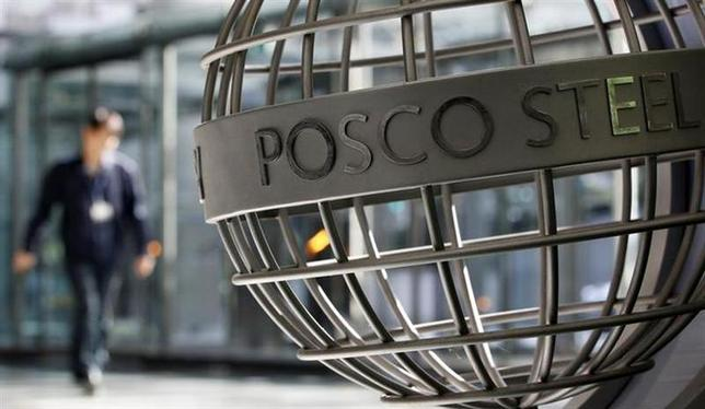 An employee of POSCO walks next to a sculpture with POSCO's logo at the company's headquarters in Seoul October 21, 2011. REUTERS/Jo Yong-Hak/Files