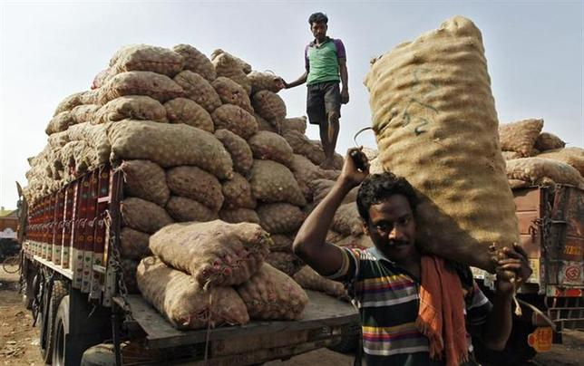 Labourers unload sacks filled with onions at a wholesale vegetable market in Chennai November 14, 2013. REUTERS/Babu/Files