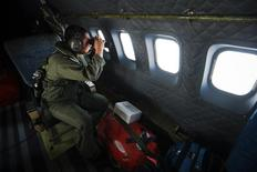 Служащий Королевских ВВС Малайзии смотрит в бинокль с борта самолета CN235 во время поисковой операции в Малаккском проливе 13 марта 2014 года. Зона поисков пропавшего почти неделю назад пассажирского самолета Malaysia Airlines может быть значительно расширена до Индийского океана, сообщил Белый дом США. REUTERS/Samsul Said