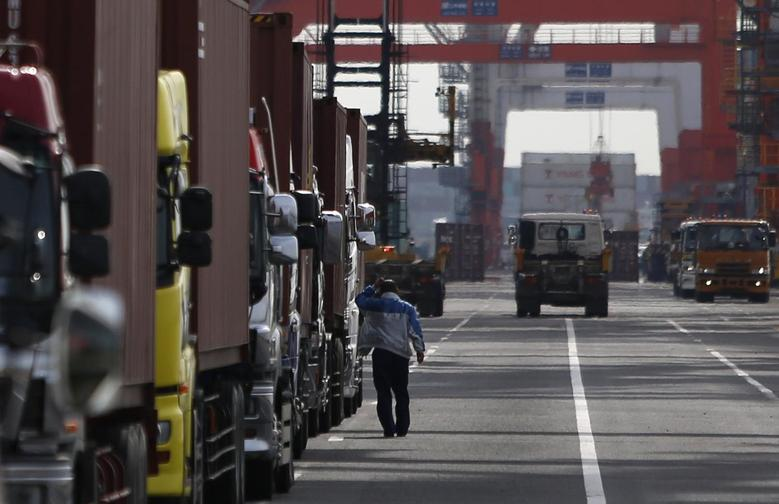 A worker scratching his head walks next to trucks parked inside a container area at a port in Tokyo February 20, 2014. REUTERS/Yuya Shino
