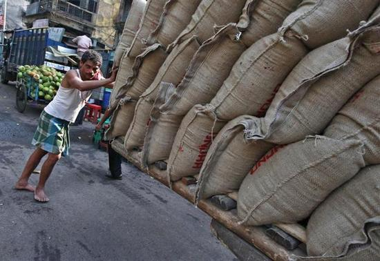 A labourer pushes a hand cart loaded with sacks of rice at a wholesale market in Kolkata March 14, 2014. REUTERS/Rupak De Chowdhuri