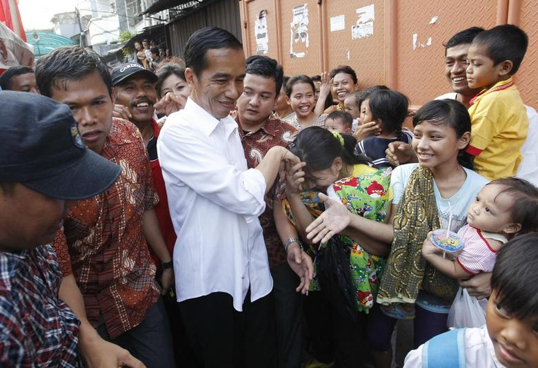 Jakarta's Governor Joko Widodo, also known as Jokowi, is greeted by residents during his visit to inspect the aftermath of a slum fire area in west Jakarta April 9, 2013. REUTERS/Enny Nuraheni
