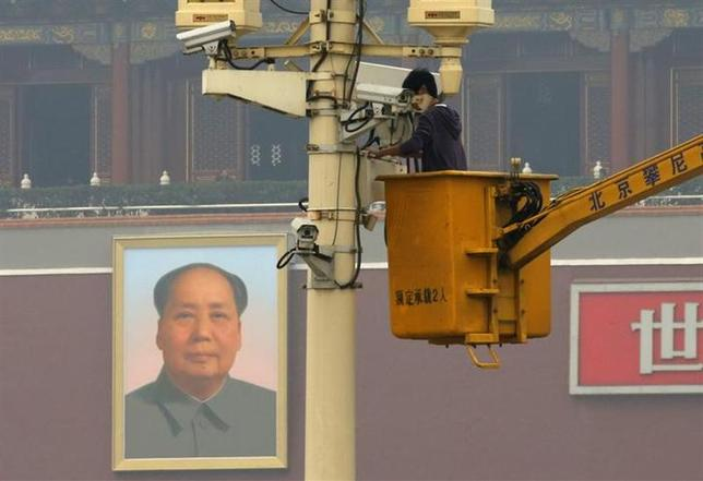 A man works on a security camera that was installed at Tiananmen Square in Beijing, November 1, 2013. REUTERS/Kim Kyung-Hoon