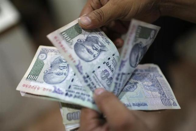 An employee counts rupee currency notes inside a private money exchange office in New Delhi July 5, 2013. REUTERS/Adnan Abidi/Files