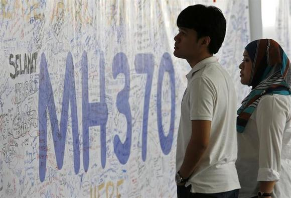 People look at a banner of well wishes for the passengers of the missing Malaysia Airlines MH370 plane at Kuala Lumpur International Airport March 14, 2014. REUTERS/Edgar Su