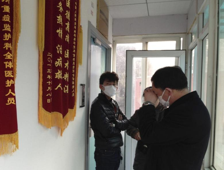 Friends of human right activist Cao Shunli stand in front of an intensive care unit where Cao is hospitalized as they are not allowed to go inside of the unit at a hospital in Beijing in this March 1, 2014 file picture. REUTERS/Kim Kyung-Hoon/Files
