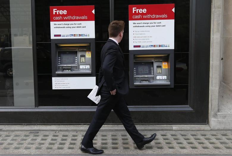 A man walks past automated teller machines (ATMs) outside a HSBC bank in London March 13, 2014. REUTERS/Suzanne Plunkett