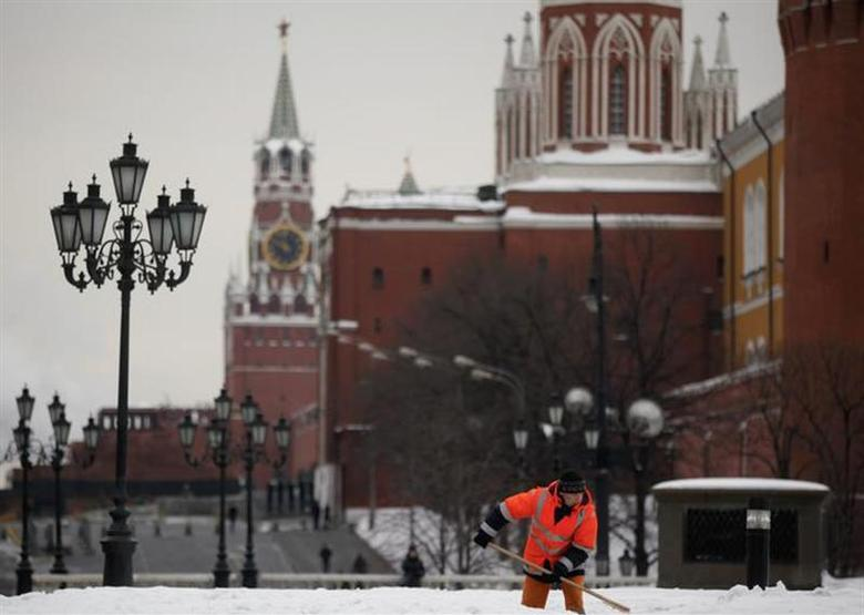 A worker shovels snow, with the Kremlin seen in the background, in central Moscow March 2, 2012. Russians will go to the polls for their presidential election on March 4, 2012. REUTERS/Pawel Kopczynski/Files