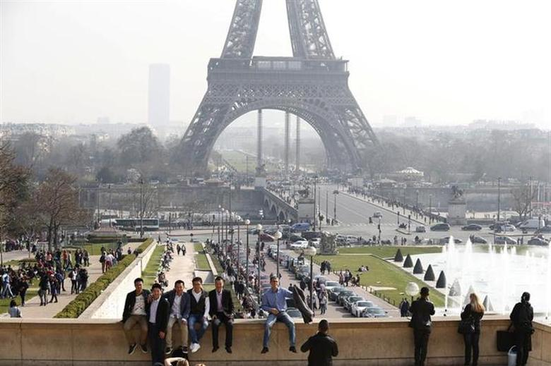Tourists enjoy the sunny weather in front of the Eiffel tower in Paris March 14, 2014. REUTERS/Charles Platiau