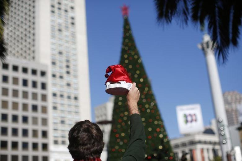 A holiday reveler holds a Santa Claus hat in front of a Christmas tree in Union Square during the annual SantaCon event in San Francisco December 14, 2013. REUTERS/Stephen Lam