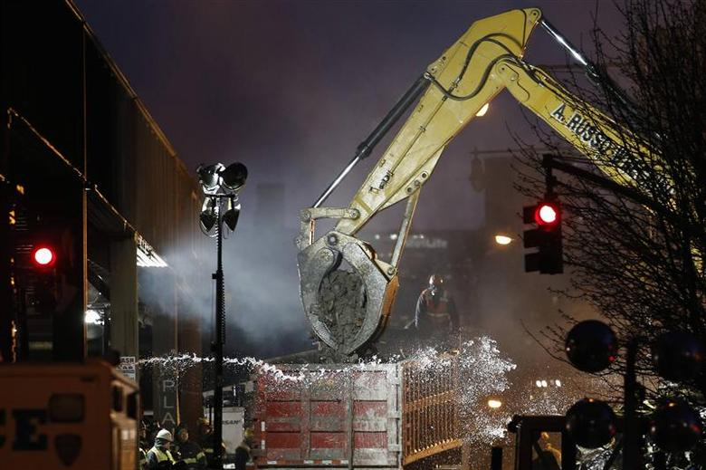 An excavator clears debris at the site of a building explosion in the Harlem section of New York, March 13, 2014. REUTERS/Eduardo Munoz