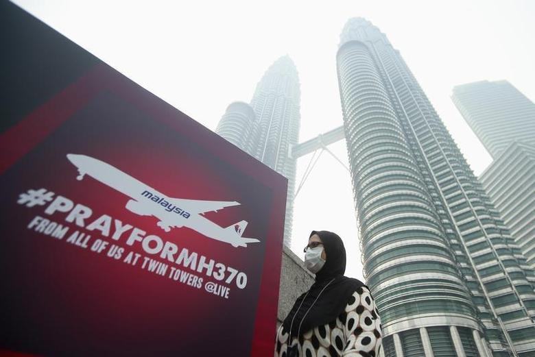 A woman wearing a mask against the haze walks past a board saying ''Pray for MH370'' in front of the Kuala Lumpur City Center (KLCC) March 14, 2014. REUTERS/Samsul Said