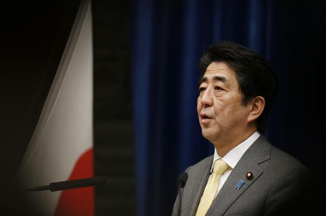 Japan's Prime Minister Shinzo Abe speaks next to the Japanese national flag, attached with a black ribbon to mourn victims during a news conference at his official residence in Tokyo March 10, 2014. REUTERS/Issei Kato