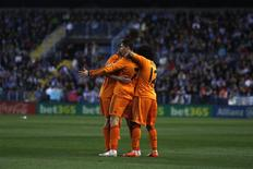 Real Madrid's Cristiano Ronaldo (C) is congratulated by his teammates after scoring a goal against Malaga during their Spanish First Division soccer match at La Rosaleda stadium in Malaga March 15, 2014. REUTERS/Jon Nazca