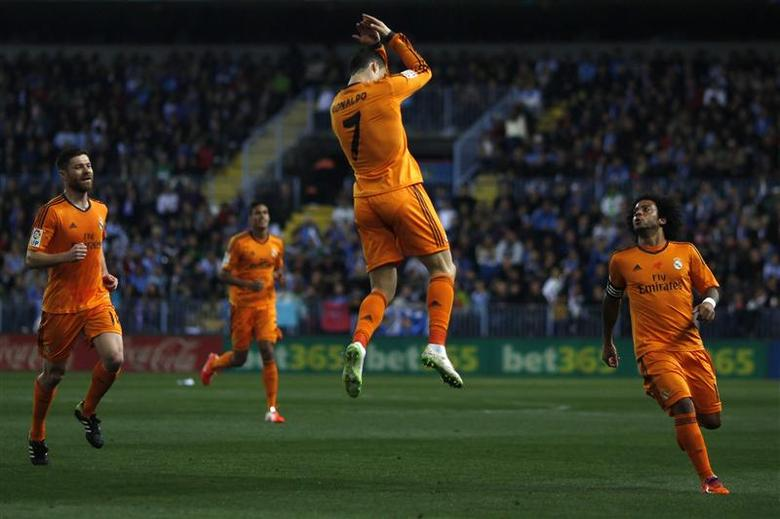 Real Madrid's Cristiano Ronaldo (C) celebrates after scoring a goal against Malaga during their Spanish First Division soccer match at La Rosaleda stadium in Malaga, southern Spain March 15, 2014. REUTERS/Jon Nazca