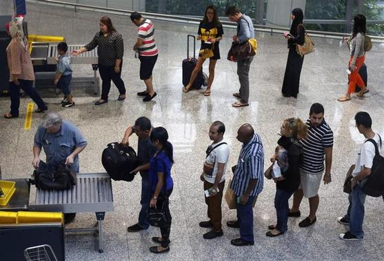 Passengers have their belongings screened by airport security at the departure hall of the Kuala Lumpur International Airport March 16, 2014. REUTERS/Edgar Su