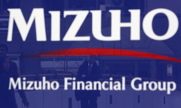 A man is reflected on an advertisement board of Mizuho Financial Group's Mizuho Bank in Tokyo January 30, 2014. REUTERS/Yuya Shino/Files