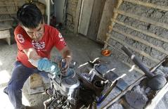 Manuel Bonilla, 62, who lost his right arm when rebels detonated a bus bomb in Toribio's central square, works on a motorcycle engine during a Reuters interview in Toribio February 6, 2014. REUTERS/Jaime Saldarriaga
