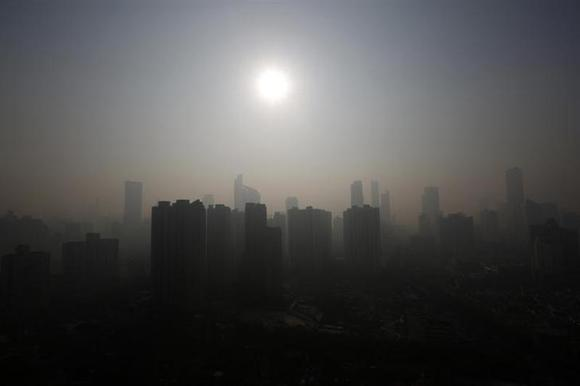 Buildings are seen through thick haze in downtown Shanghai November 7, 2013. REUTERS/Aly Song/Files
