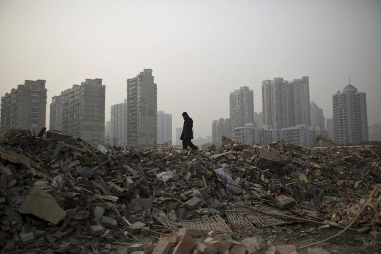 A man walks in an area where old residential buildings are being demolished to make room for new skyscrapers in central Shanghai January 20, 2014. REUTERS/Aly Song