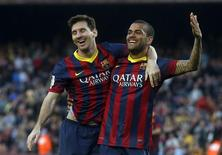 Barcelona's Lionel Messi (L) and Dani Alves celebrate a goal against Osasuna during the Spanish first division soccer match at Camp Nou stadium in Barcelona March 16, 2014. REUTERS/Albert Gea