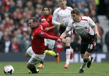 Liverpool's Jon Flanagan (R) pulls back Manchester United's Wayne Rooney during their English Premier League soccer match at Old Trafford in Manchester, northern England, March 16, 2014. REUTERS/Phil Noble