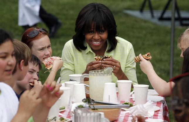 U.S. first lady Michelle Obama eats with school kids after they harvested vegetables from the summer crop from inside the White House Kitchen Garden on the South Lawn in Washington, May 28, 2013. REUTERS/Larry Downing