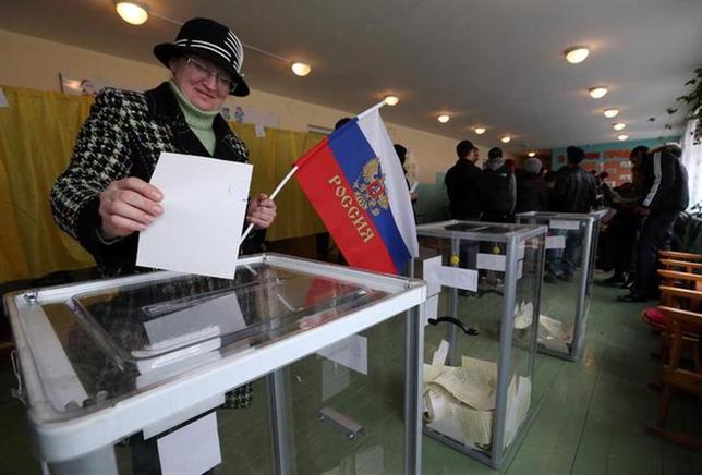 3月16日、ウクライナ南部・クリミア半島で実施されたロシア編入の是非を問う住民投票で、地元選挙管理委員会は、開票率50%以上の段階で、95.5%がロシア編入を支持したことを明らかにした。写真はバフチサライでロシア国旗を手に投票する女性(2014年 ロイター/Sergei Karpukhin)