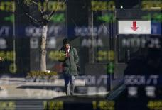 A man is reflected in a stock quotation board outside a brokerage in Tokyo January 28, 2014. REUTERS/Toru Hanai