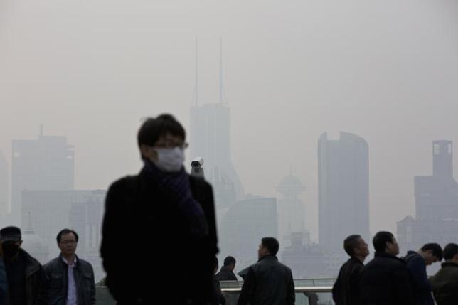 A man wearing a face mask walks through the Lujiazui financial district of Pudong on a hazy day in Shanghai, March 10, 2014. REUTERS/Aly Song