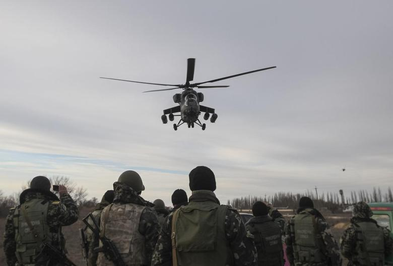A Russian army MI-35 military helicopter patrols the area as Ukrainian servicemen guard a checkpoint near the village of Strelkovo in Kherson region adjacent to Crimea, March 16, 2014. REUTERS/Valentyn Ogirenko