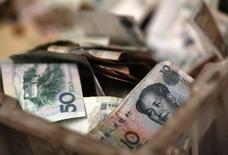 Деньги в коробке у продавца на рынке в Пекине 14 февраля 2014 года. Центробанк Китая в субботу ослабил контроль над юанем, расширив дневной торговый диапазон вдвое, чем подтвердил обещание позволить рыночным силам играть более значительную роль в экономике и на рынках. REUTERS/Kim Kyung-Hoon