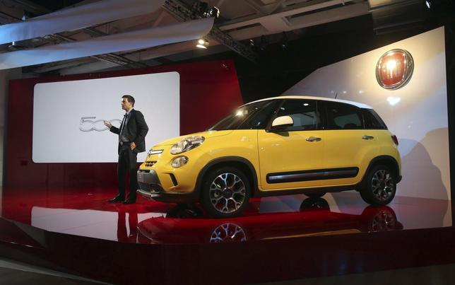 Jacob Nyborg, communication and marketing manager of Fiat Chrysler EMEA, stands next to the new Fiat 500L Living and Trekking model during a presentation in Arcore July 4, 2013. REUTERS/Stringer