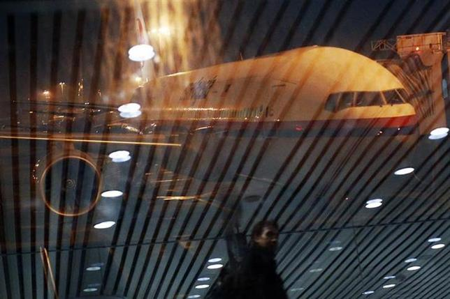 Malaysia Airlines Boeing 777-200ER flight MH318 to Beijing sits on the tarmac as passengers are reflected on the glass at the boarding gate at Kuala Lumpur International Airport at approximately 12:20am March 17, 2014. REUTERS/Edgar Su