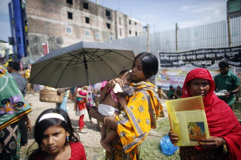 A garment worker who survived the Rana Plaza building collapse, carries her child during a protest to demand for compensation, on the six month anniversary of the incident, in front of the site in Savar October 24, 2013. REUTERS/Andrew Biraj