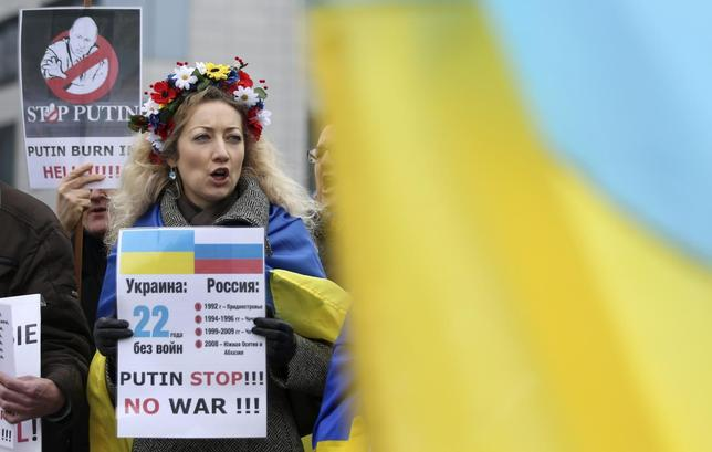 A demonstrator holds a placard and chants slogans against Russian President Vladimir Putin during a protest against Russia's incursion into Crimea, outside a meeting of European Union foreign ministers in Brussels March 17, 2014. REUTERS/Francois Lenoir