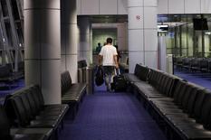 Passageiros se preparam para embarcar em um voo da Malaysia Airlines para Pequim, no aeroporto internacional de Kuala Lumpur. A Austrália assumiu nesta segunda-feira o rastreamento do sul do oceano Índico em busca de um avião desaparecido, e a Malásia solicitou dados de radar de países que vão até a Ásia Central, em meio a crescentes evidências de que o desaparecimento do avião foi meticulosamente planejado. 17/03/2014 REUTERS/Edgar Su