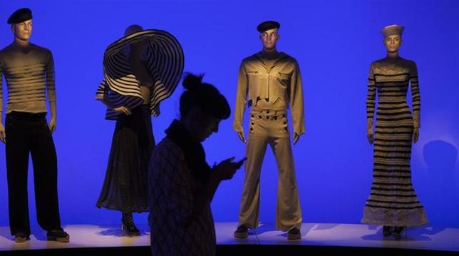A woman looks at her phone as she walks past mannequins displaying the creations of designer Jean Paul Gaultier at an exhibition of his works in the Brooklyn borough of New York, October 23, 2013. REUTERS/Carlo Allegri/Files