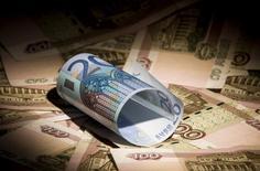 Uma nota de euro e notas de rublos russos vistas nesta fotoilustração, em Moscou. O índice de inflação na zona do euro atingiu o menor nível anual em 4 anos em fevereiro, mostraram dados revisados nesta segunda-feira, desacelerando para a mesma taxa que levou o Banco Central Europeu a reduzir de forma inesperada os juros em novembro. 17/02/2014 REUTERS/Maxim Shemetov