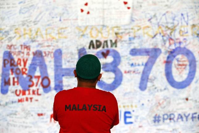 A man stands in front of a board with messages of hope and support for the passengers of the missing Malaysia Airlines MH370 at the departure hall of the Kuala Lumpur International Airport March 17, 2014. REUTERS/Damir Sagolj