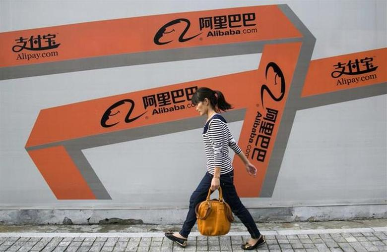 A woman walks past an Alibaba advertisement on a wall in Hangzhou, Zhejiang province September 26, 2013. REUTERS/Chance Chan/Files